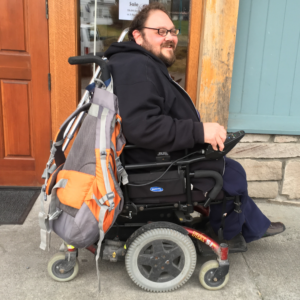 Man with a beard and black sweatshirt uses a wheelchair on the sidewalk in front of a building